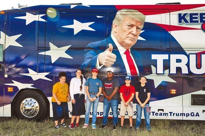 在美國喬治亞州梅肯市,幾名川粉16日在一輛有川普競選宣傳圖像的大巴士前拍照留念。(路透)
