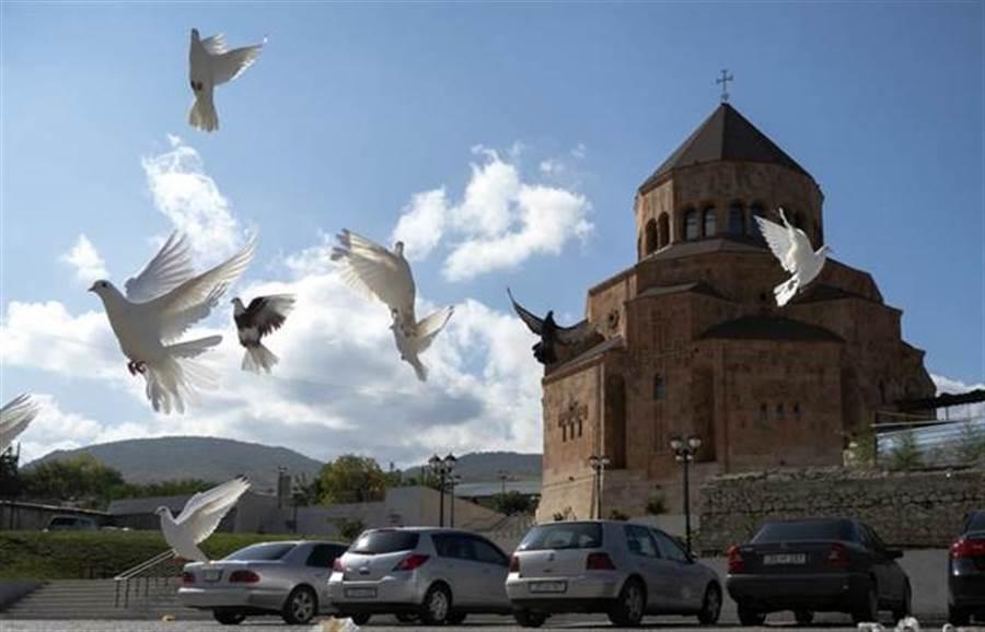 亞美尼亞和亞塞拜然同意 18日起人道停火。圖為位於引起亞美尼亞與亞塞拜然衝突的卡拉巴赫地區,一座聖母院大教堂附近飛滿了鴿子。(美聯社)