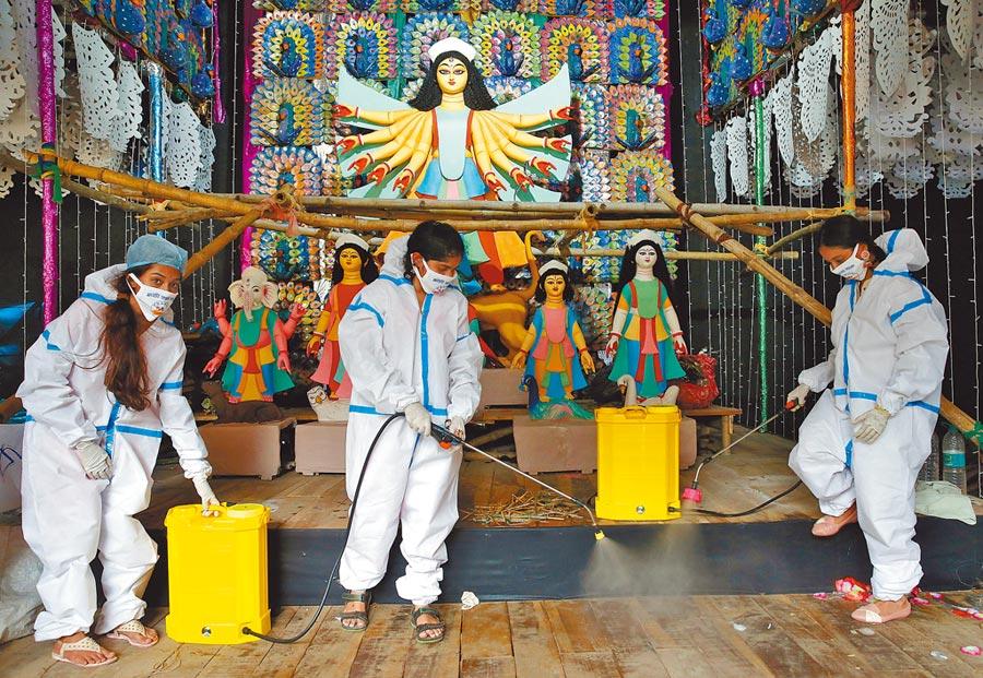 印度加爾各答市一處為迎接「杜爾加女神」(Durga Puja)而臨時搭建的舞台,幾名婦女16日穿著防護衣進行消毒工作。印度新冠疫情正迅速擴大,確診人數逐漸逼近美國,不久或將超越美國,成為全球染疫人數最多的國家。(路透)
