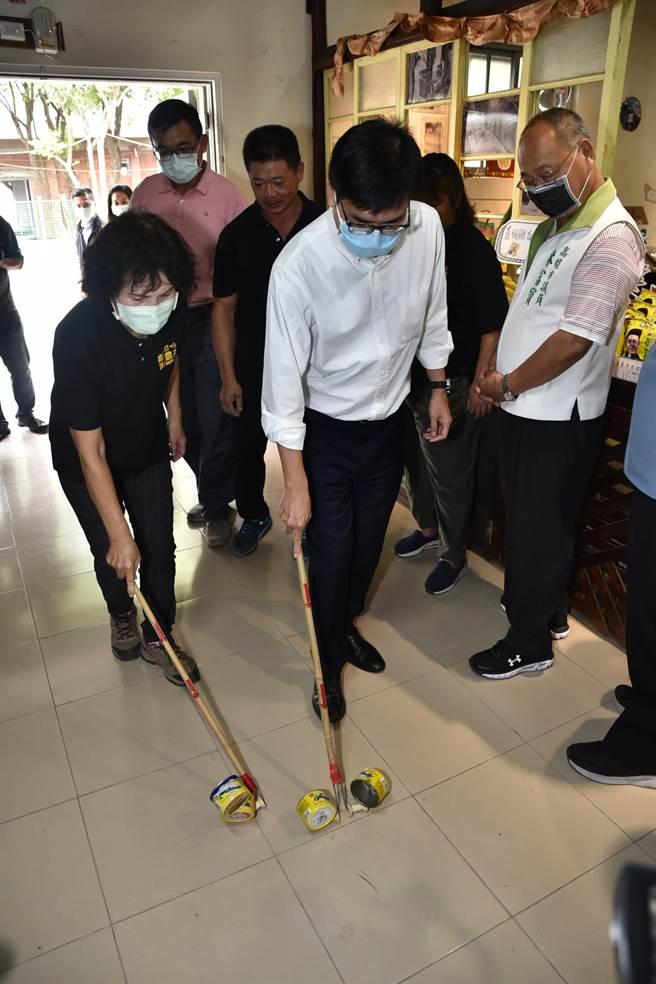 高雄市長陳其邁(前右)19日走訪旗山區糖廠社區,試玩用竹棍與空罐頭組合而成的童玩。(林瑞益攝)