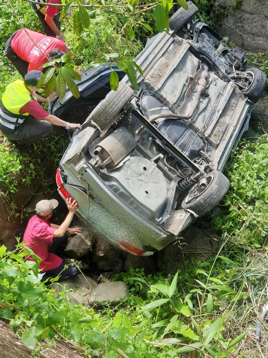 鍾氏夫婦座車衝落5米深的溪底,消防隊員以破壞器材打開車門救出4人。(消防局提供/謝明俊苗栗傳真)