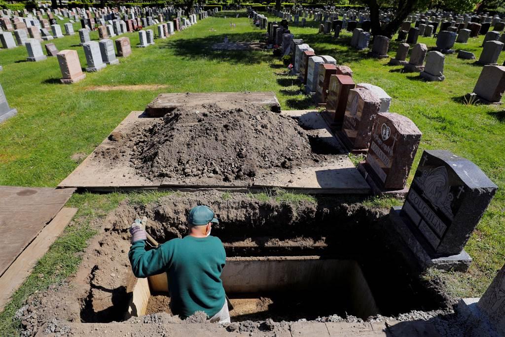 美國麻薩諸塞州一處墓園,工人正忙著挖掘新的墓穴。(路透)