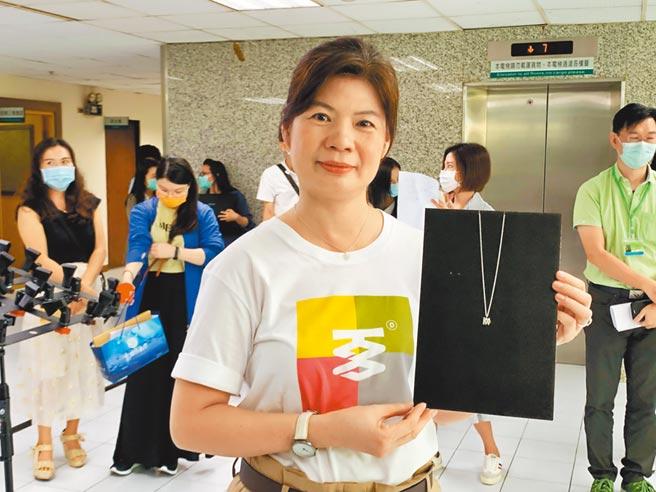 「高雄一百」系列活動10月中開跑,高市文化局長王文翠身穿LOGO T恤介紹文創項鍊。(柯宗緯攝)