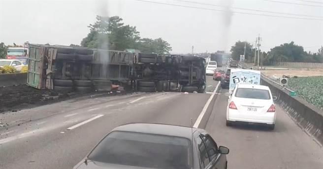 國道一號北上337.2公里路竹路段22日中午12時19分發生車禍,1部砂石車翻車側翻,砂石傾倒在路面上,還因此波及一輛小客車。(翻攝照片/林瑞益高雄傳真)