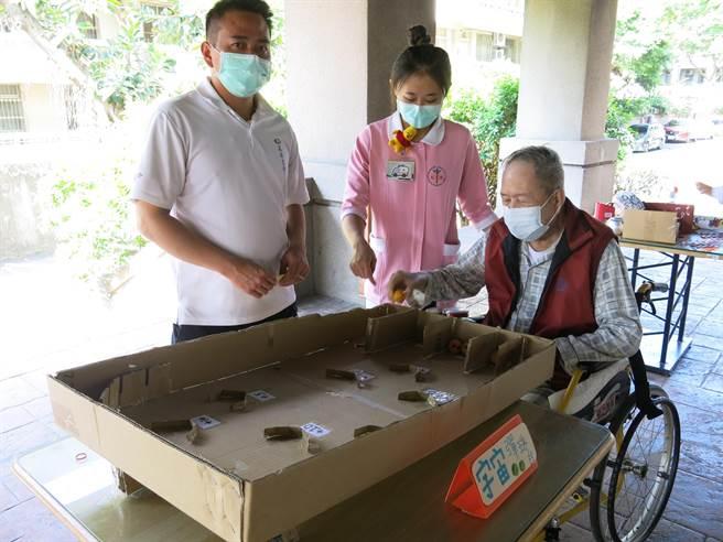 豐原醫院附設護理之家舉辦「豐原柑仔店」,住民阿公體驗挑戰彈珠台。(王文吉攝)