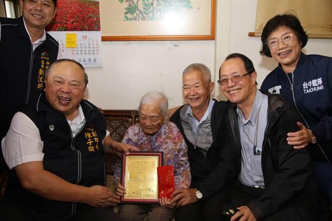 台中市副市長陳子敬(左)致贈百歲人瑞王張蜜敬老狀與重陽禮金。(王文吉攝)