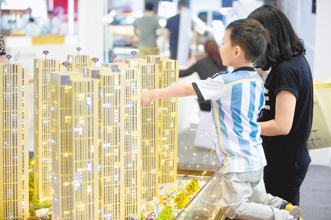 山西太原一名兒童陪父母看樓房模型。(中新社資料照片)