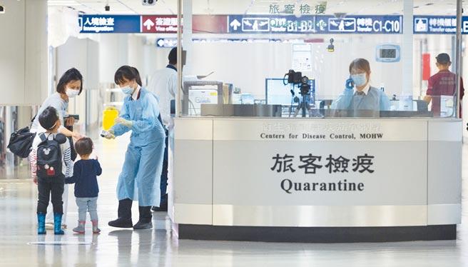 10月22日,桃園機場入境旅客填寫完入境檢疫表後,前往檢疫站由疫管局人員檢測體溫。(本報系記者陳麒全攝)