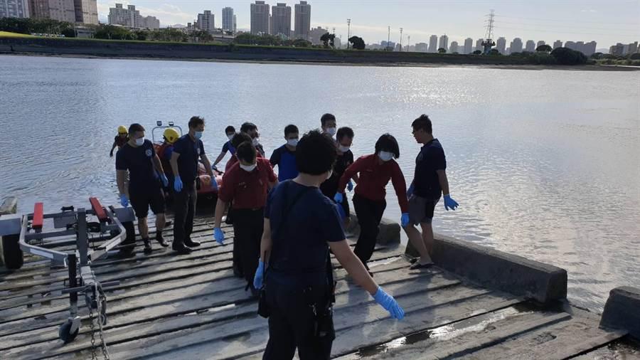 22日中正橋落水的鄧姓工人,今下午被發現在事發地下游200公尺,警消根據身上穿著的裝備確認身分,並協助打撈上岸。(民眾提供/李文正台北傳真)