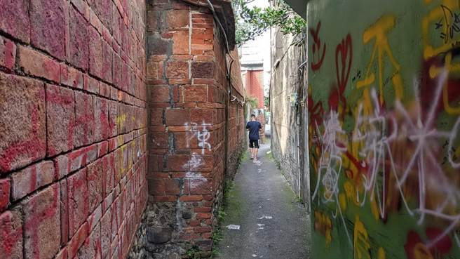 屏東潮州鎮摸乳巷的百年老厝紅磚牆壁近日遭人噴漆塗鴉,難以清除,讓屋主十分火大,網友也痛批「水準太低!」(潘建志攝)