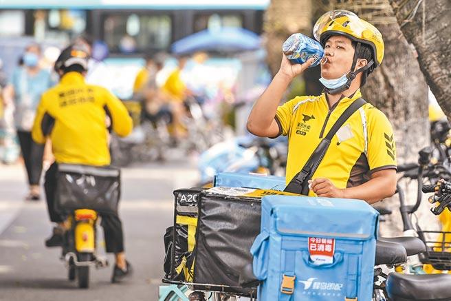 廣東廣州市天河區,一名外賣配送員喝飲料解渴。(中新社資料照片)