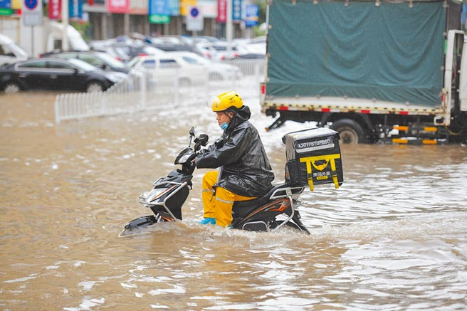遼寧瀋陽,外賣員騎車經過一段積水路面。(中新社資料照片)