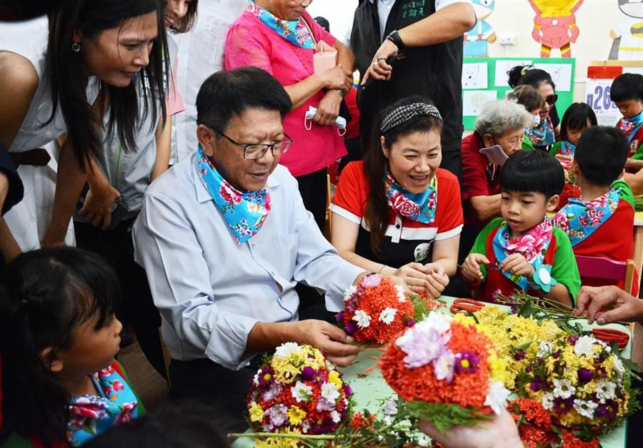 屏東縣長潘孟安(左二)參加長興非營利幼兒園揭牌,更走進教室與學童體驗製作客家盤花。(林和生攝)