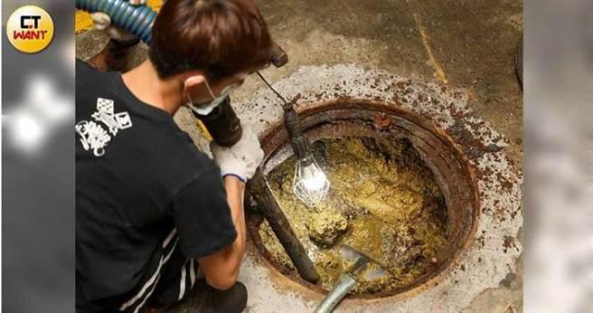 師傅將化糞池孔蓋撬開後,得先面臨蜂擁而出的蟑螂蚊蟲,再克服撲鼻臭味抽取水肥,任務艱鉅而辛苦。(圖/張文玠攝)