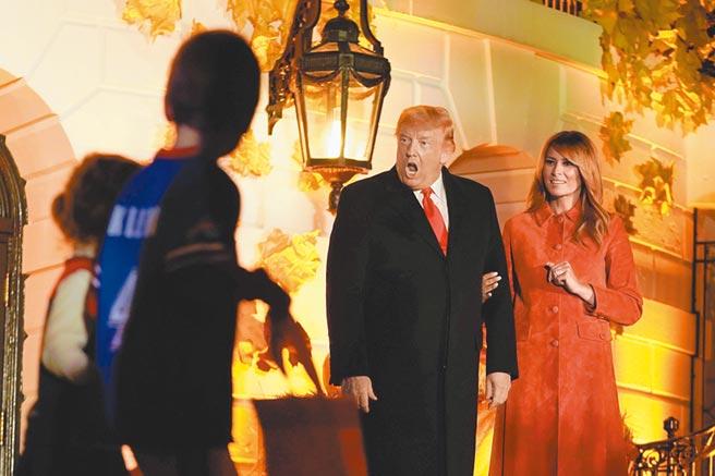 美國總統川普忙裡偷閒,25日與第一夫人梅蘭妮亞分送糖果,給前來白宮參加萬聖節慶祝活動的孩童。(路透)