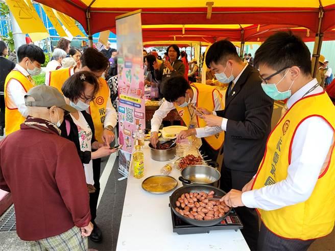 永慶夥伴熱情烹調美味的烤香腸與里民同歡。(圖/業者提供)