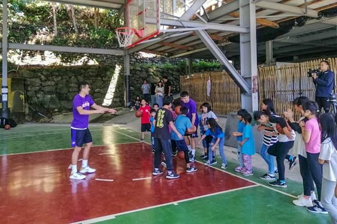 新竹攻城獅隊球員高國豪和田浩在新光國小司馬庫斯實驗分班,進行公益籃球教學與小朋友一起打籃球。(縣府提供/羅浚濱新竹傳真)