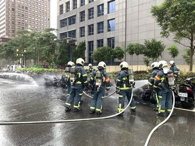 北市信義區路邊機車起火,消防人員到場灌救。(翻攝照片/林郁平台北傳真)