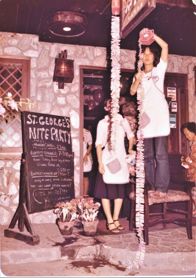 妹妹在餐館舉辦的St. George's Nite Party,布置會場。只見她穿著員工制服,在餐館門口,身先士卒,爬上椅子,掛起一串又一串的鞭炮,準備迎接客人到來。(羅青提供)