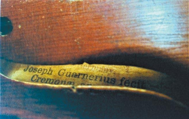 往f型音孔裡瞧,音箱背板依稀可以分辨寫的是Joseph Guarnerius fecit。(羅青提供)