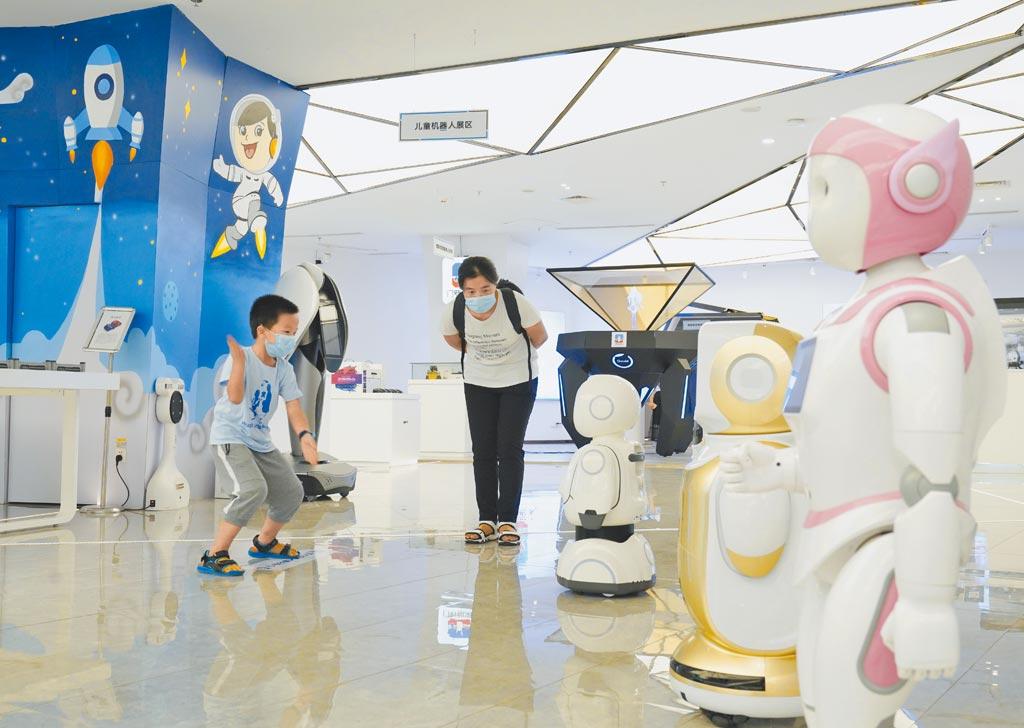 8月15日,重庆两江机器人展示中心,一名男孩与机器人互动。 (新华社)