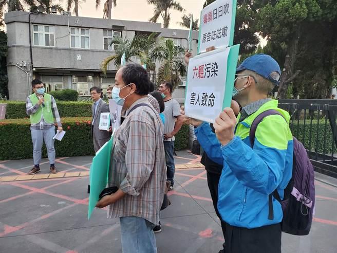 向六輕廠區內5家公司求償的林姓麥寮鄉民(右一)親自聆判,聽到法院宣判駁回不表示看法,持手拿牌呼口號「六輕汙染害人致命」。(周麗蘭攝)