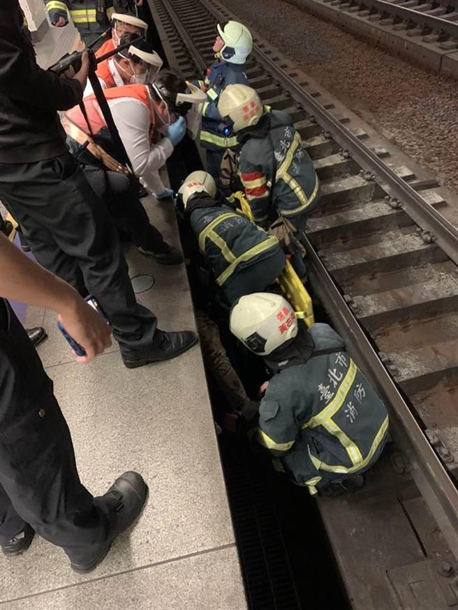 救护人员协助男子脱困后,将他送往北医救治。(翻摄照片/林郁平台北传真)