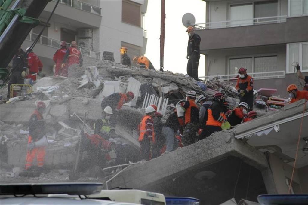 搜救人員徒手挖掘,試圖在斷垣殘壁間找到倖存者。(圖/美聯社)