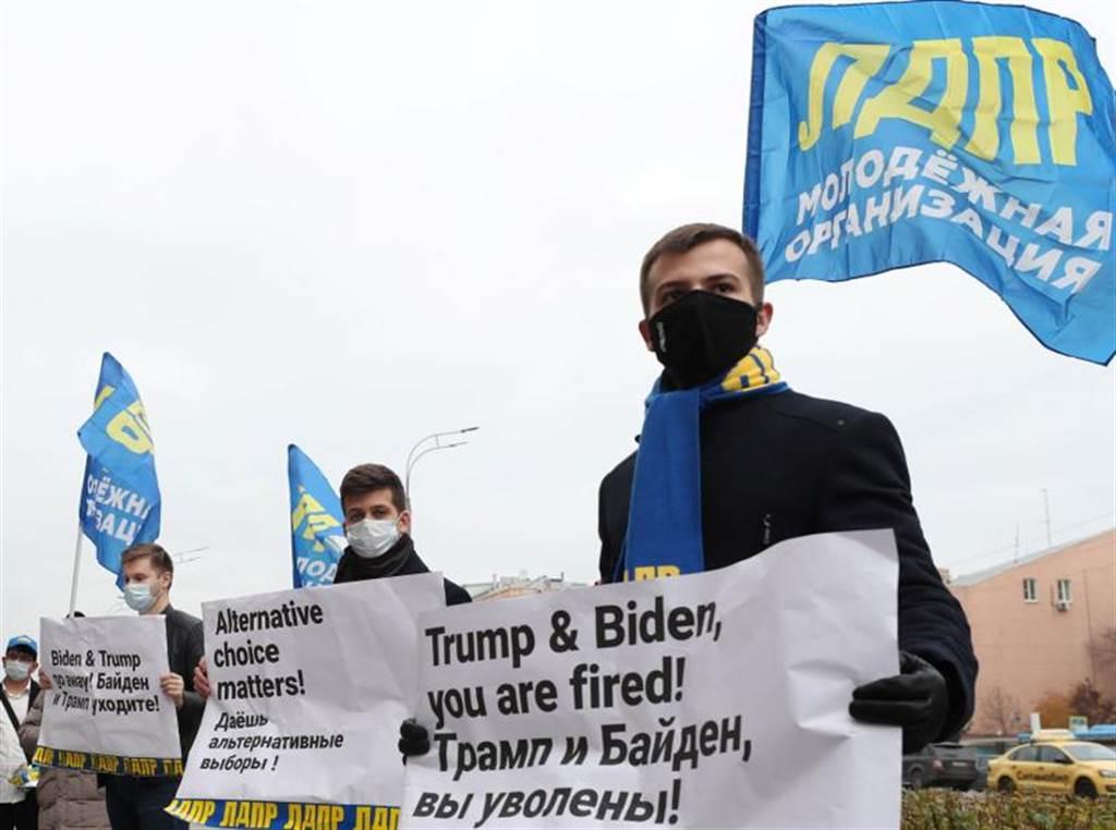 極右派「俄羅斯自由民主黨」的活躍分子戴著口罩,31日在美國駐莫斯科大使館前舉行示威活動,手拿海報寫著:「川普和拜登,都該被炒魷魚」。(路透)