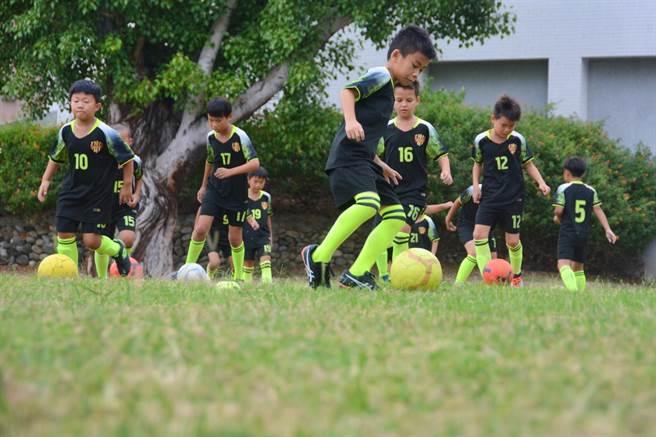 高雄市河堤國小足球隊球員珍惜1周2小時在學校操場草地上練球的機會。(林宏聰攝)