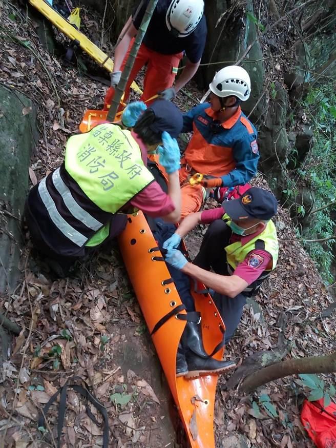 苗栗男子登山不慎跌落10公尺深的邊坡,苗栗縣消防局獲報以捲式擔架搬運救出。(苗栗縣消防局提供/何冠嫻苗栗傳真)