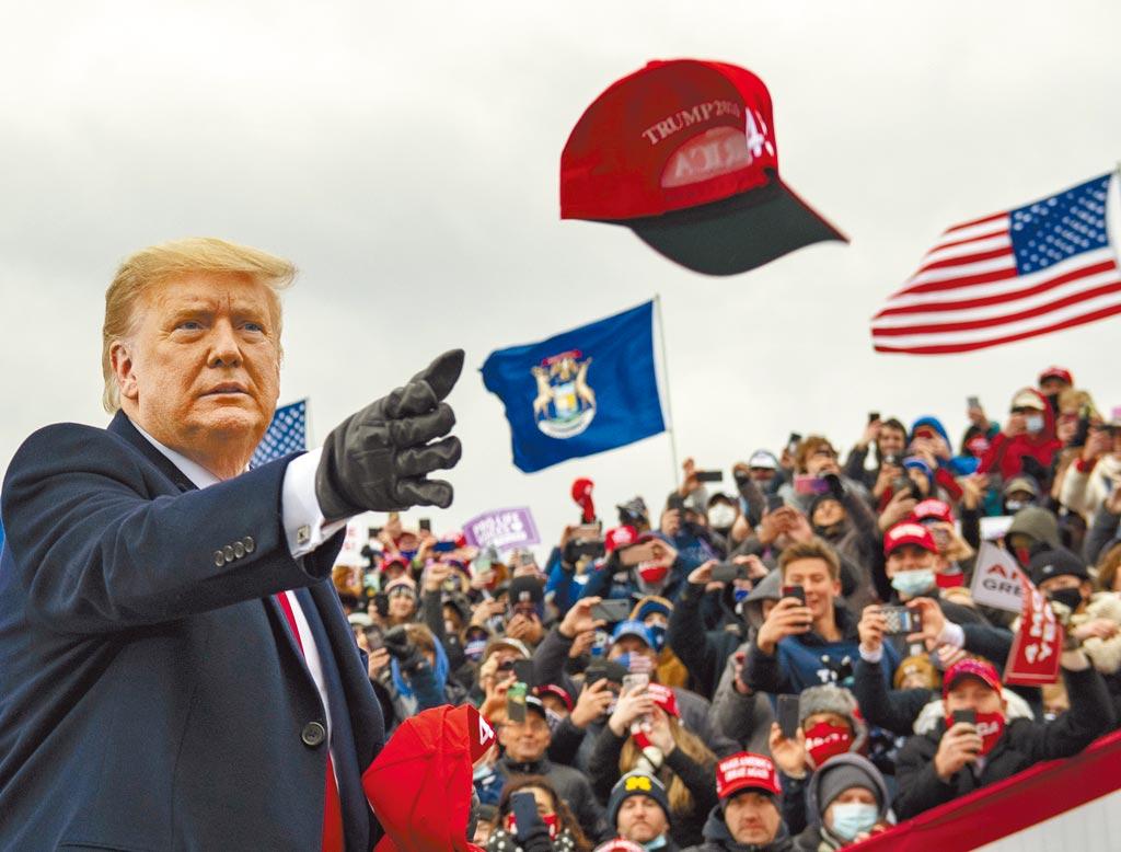 美國總統川普10月30日在密西根州的一場造勢活動上,將所戴的一頂帽子扔給支持者。(美聯社)