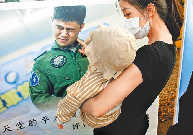 殉職飛官朱冠甍的滿周歲女兒,由親人抱著,凝視著已經在天上的爸爸遺容,令人鼻酸。(莊哲權攝)