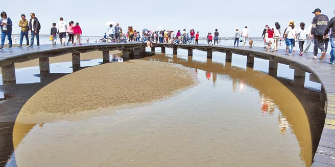 高美溼地遊客漫步在木棧道上近距離觀察水棲生態。(陳淑娥攝)