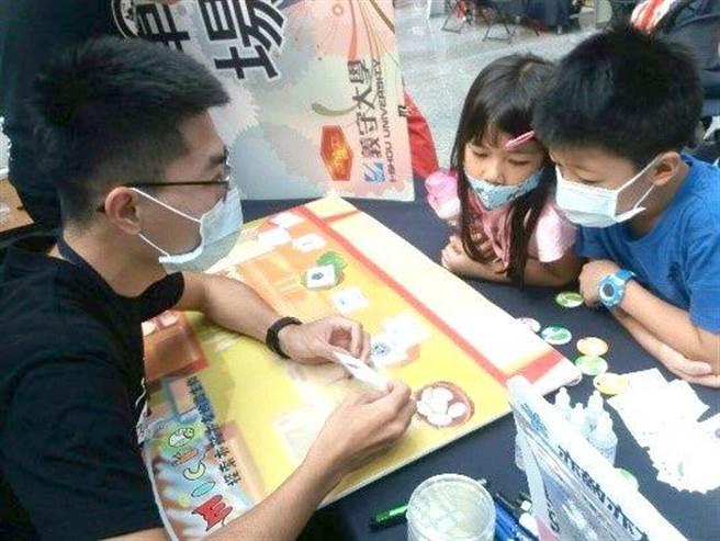 義大學生利用牌卡設計遊戲,拉近小朋友和科普知識的距離。(義守大學提供/林雅惠高雄傳真)