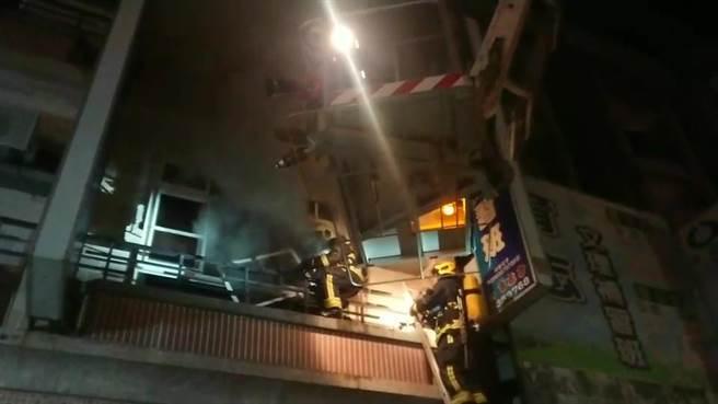 嘉義市透天厝凌晨失火,消防員架梯搶救,同時雲梯車出動。(讀者提供)
