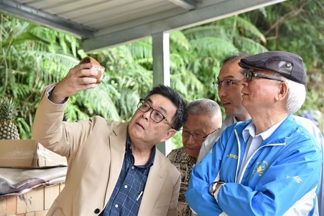 華梵大學校長李天任(左)與同仁仔細端詳華梵窯的首燒成果。(華梵大學提供)