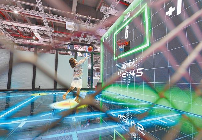 11月5日,第三屆中國國際進口博覽會消費品展區,一家體育用品公司的展台,參會者體驗籃球互動遊戲。(中新社)