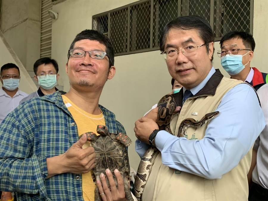 台南市長黃偉哲(右)7日出席動保宣傳活動,巧遇民眾帶著陸龜、球蟒參加,並邀請黃偉哲與寵物合影。(李宜杰攝)