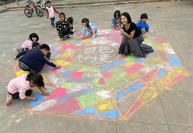 藝術家成若涵與小朋友在「國姓井」的輪廓中,攜手彩繪在地的故鄉情。(金門縣府觀光處提供)