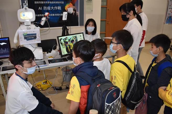 國衛院科普日展出AI智慧防疫機器人,吸引小朋友好奇觀看。(謝明俊攝)