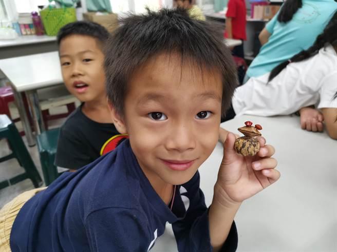 鄭美蓮到台南市口埤國小教小朋友以相思豆、石栗種子做成可愛的青蛙。(劉秀芬攝)