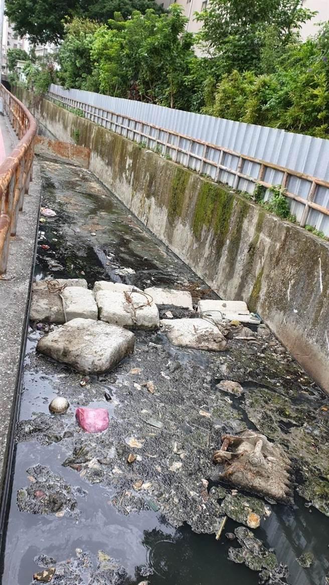 施工單位將清淤工具棄置在水溝內,讓垃圾更容易堆積在內,引起陣陣惡臭。(蔡健棠服務處提供/李俊淇新北傳真)
