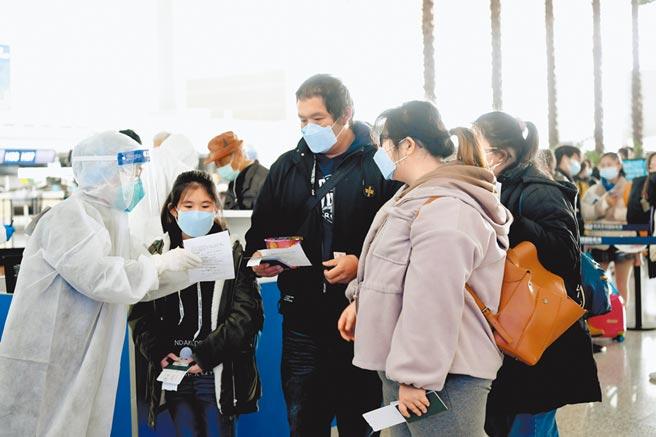 3月10日,湖北台胞搭乘航班,從武漢返回台灣,工作人員在核對乘客資料。(中新社)