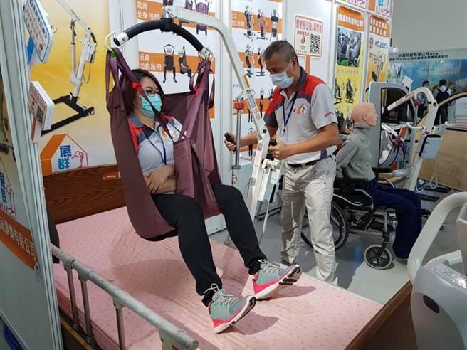 展群福祉事業工作人員,示範使用迷你電動移位機,將長者從起居室,安全的移動到臥床。圖/顏瑞田攝