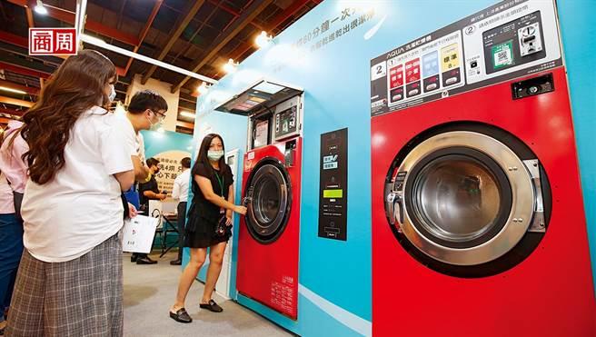 10月台北國際加盟展中,自助洗衣店加盟總部員工,正向加盟主說明洗脫烘三合一的洗衣設備優勢。(圖/商業周刊提供、駱裕隆攝)
