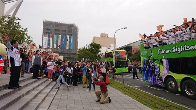 臺南市長黃偉哲(左邊西裝褲者)以統一獅熟悉的打氣加油方式,比出大鳥飛翔知識,車上球員見狀驚喜熱情回應。(程炳璋攝)