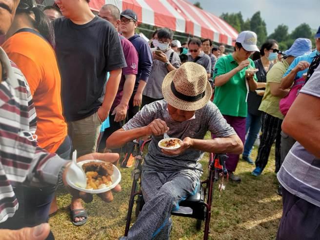 一名老者坐在两摊滷肉饭选手前开吃。(周丽兰摄)