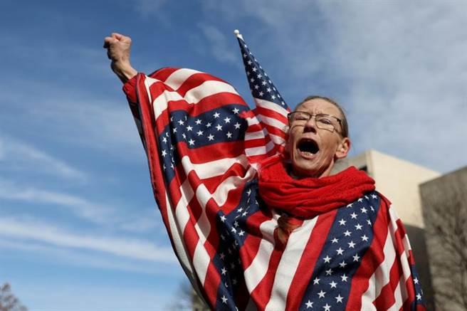 美國大選落幕近2周。美媒統計,總統當選人拜登共可拿下306張選舉人票,現任總統川普則是232票。圖為1名「鐵桿川粉」身披美國國旗,參加14日密西根州的「停止偷竊大選」遊行活動。(路透)