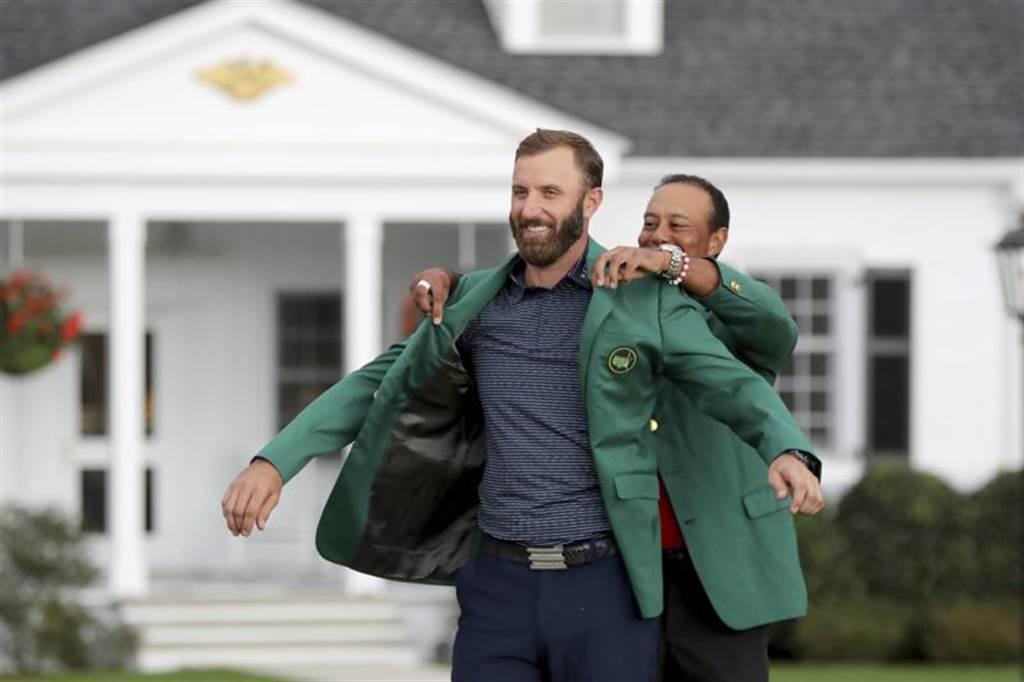 世界球王強生在美國名人賽以破紀錄的低於標準20桿268總桿奪冠,老虎伍茲親自為強生穿起象徵榮耀的綠夾克。(美聯社)